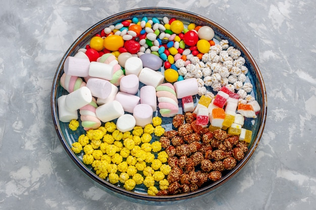 Top view candy composition different colored candies with marshmallow on light-white desk sugar candy bonbon sweet confiture