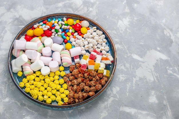 Top view candy composition different colored candies with marshmallow on the light white desk sugar candy bonbon sweet confiture