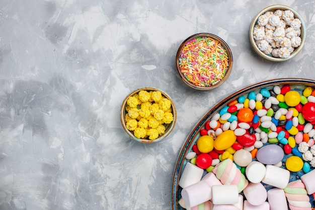 Top view candy composition different colored candies with marshmallow on white desk sugar candy bonbon sweet confiture tea