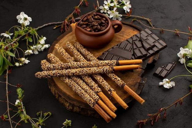 Vista dall'alto caramelle bastoncini di cioccolato insieme a semi di caffè sulla scrivania marrone e scuro