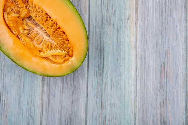 Top view of cantaloupe melon slice on grey wood with copy space