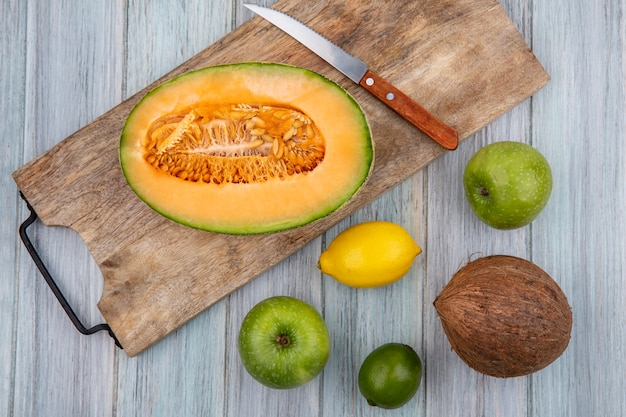 Top view of cantaloupe melon slices on wooden kitchen board with knife with coconut apples lemon on grey wood
