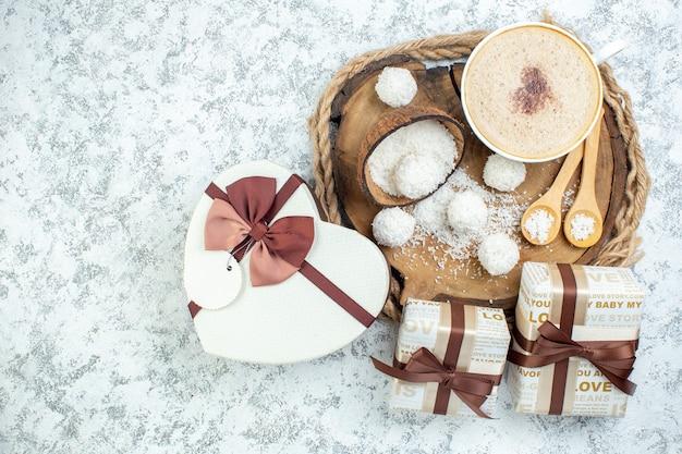Vista dall'alto tazza cappuccino polvere di cocco ciotola cucchiai di legno su tavola di legno regali a forma di cuore confezione regalo su superficie grigia