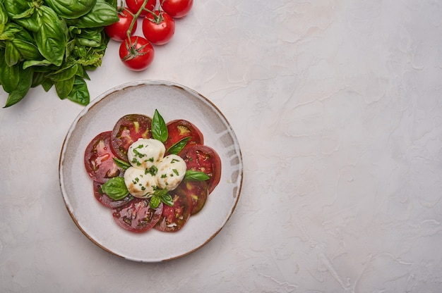 Top view caprese salad with red tomatoes fresh basil and mozzarella cheese in white plate copy space