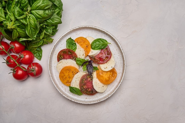 Top view caprese salad with red and yellow tomatoes fresh basil and mozzarella cheese in white plate