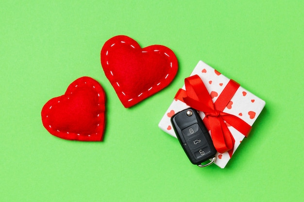 Top view of car key on gift box and red textile hearts