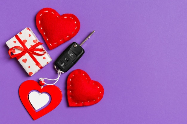 Top view of car key, gift boxes and toy hearts