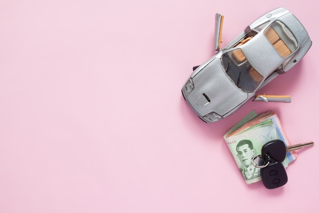 Top view of car model and thai banknotes on pink colour background with copy space