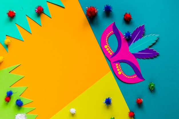 Top view of carnival mask and colorful pom-poms