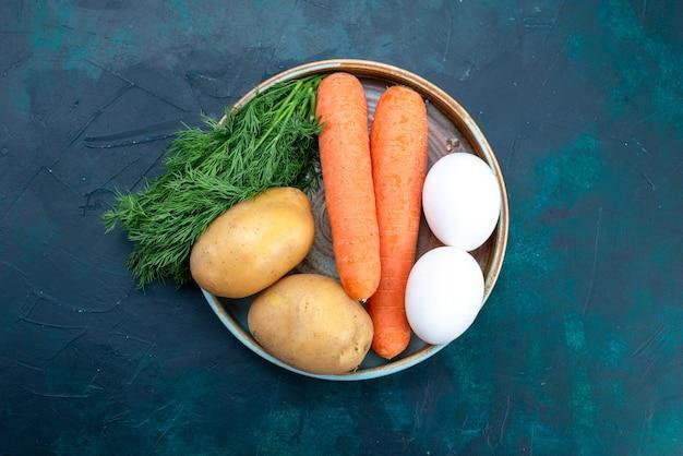 진한 파란색 책상에 계란과 채소와 함께 당근과 감자를 봅니다.