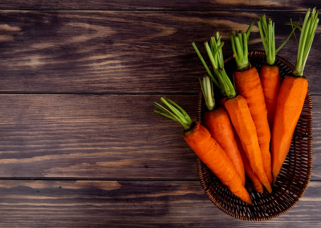 Top view of carrots in basket on wooden background with copy space