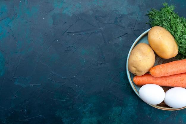 Vista dall'alto carote e patate con uova e verdure sulla scrivania blu scuro.