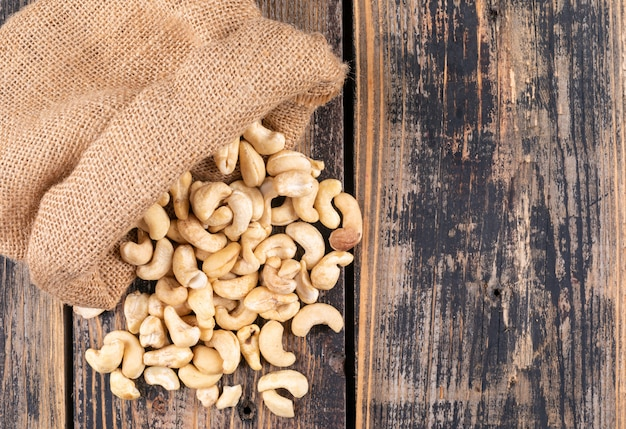 Top view cashews in sack on wooden table
