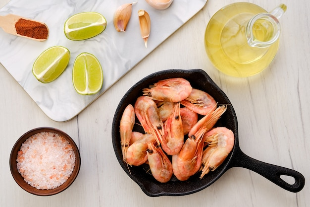 Top view of cast iron skillet with steamed unpeeled shrimps with spice