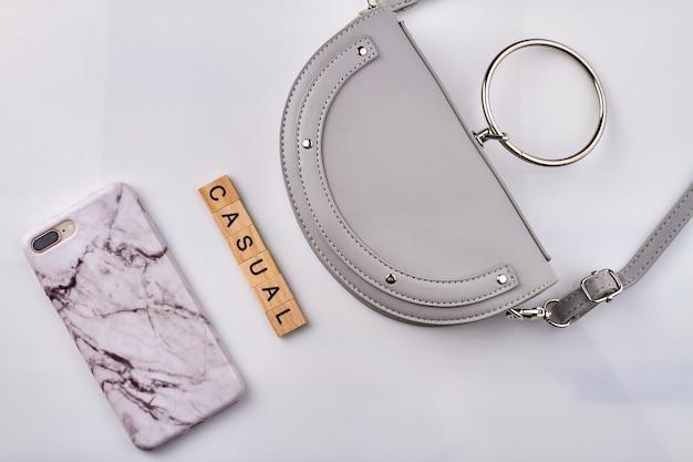 상위 뷰 캐주얼 여성 액세서리. 화이트 핸드백과 흰색 바탕에 케이스와 스마트 폰.