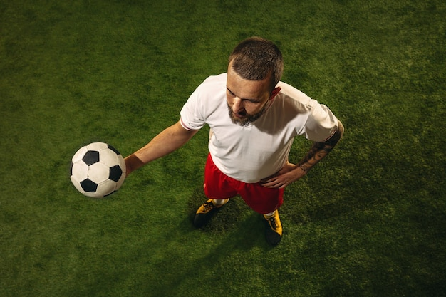 Top view of caucasian football or soccer player on grass. young male sportive model training, practicing. kicking ball, attacking, catching. concept of sport, competition, winning.