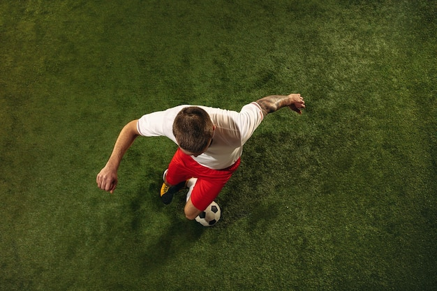 Top view of caucasian football or soccer player on green background of grass. young male sportive model training, practicing. kicking ball, attacking, catching. concept of sport, competition, winning.