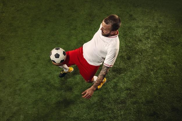 Vista dall'alto del calcio caucasico o giocatore di calcio su sfondo verde di erba. giovane maschio modello sportivo formazione, pratica. calciare la palla, attaccare, prendere. concetto di sport, competizione, vincita.