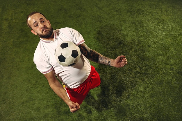 Top view of caucasian football or soccer player on green wall of grass.