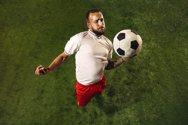 Top view of caucasian football or soccer player on green