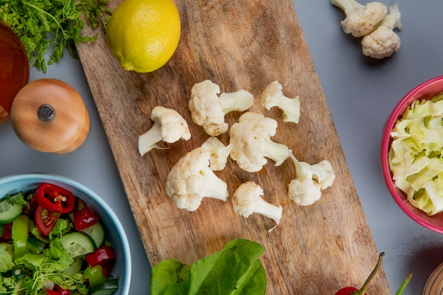 Top view of cauliflower pieces with spinach lemon on cutting board with cabbage slices coriander salt and vegetable salad on blue background