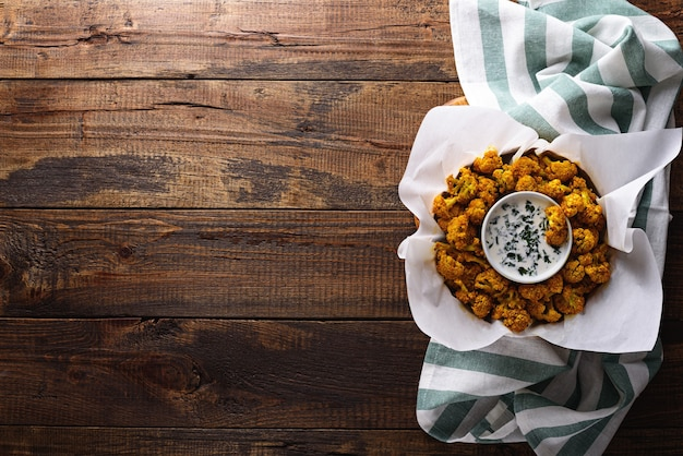 Top view cauliflower with breadcrumbs and spices with sour cream sauce and greens on wooden background with copy space. crispy vegetable snack
