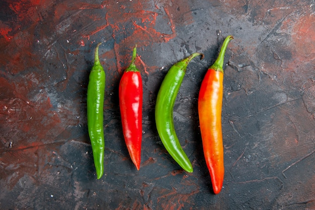 Top view of cayenne peppers in different colors and sizes on mixed color background