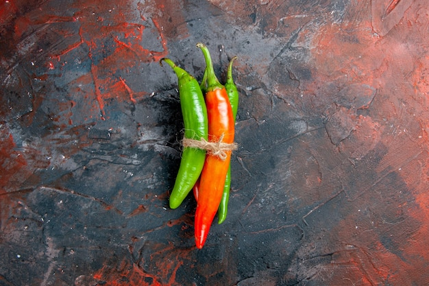 Top view of cayenne peppers in different colors and sizes tied in one another with rope on mixed color background