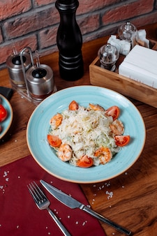 Top view of ceasar salad with shrimps and parmesan cheese on the table
