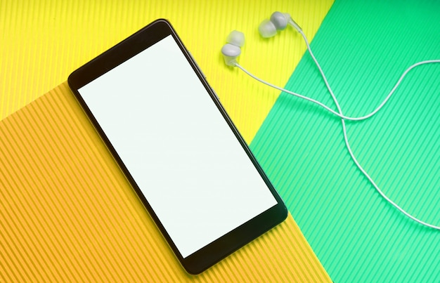 Top view of cell phone with headphones on trendy multicolor surface