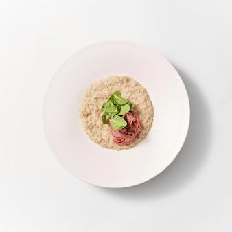 Вид сверху керамическая большая тарелка домашней овсяной каши с органическими листьями шпината и нежирной ветчиной на светло-сером фоне, копией пространства. концепция диетического питания.