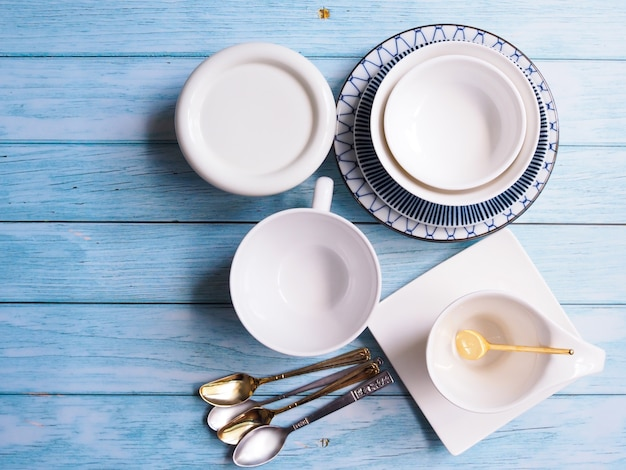 Top view of ceramic tableware set with round dish plates, crockery tea cup bowl and teaspoons on wooden table.