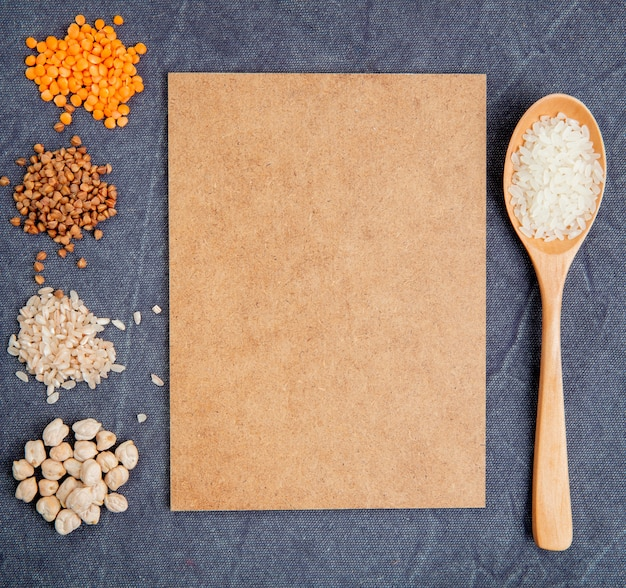Top view of cereal grains and seeds heaps chickpeas rice buckwheat and red lentils with brown sheet of paper and a wooden spoon on gray background