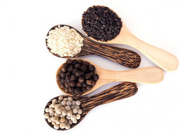 Top view of cereal herbs in wooden spoon with white pepper, black pepper, black sesame and white sesame isolated on white surface.