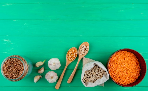 Top view of cereals and legumes assortment - buckwheat corn seeds chickpeas beans and red lentils on green wooden surface with copy space
