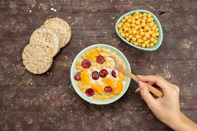 Top view cereals with milk inside plate with crackers on brown, drink milk dairy creamery