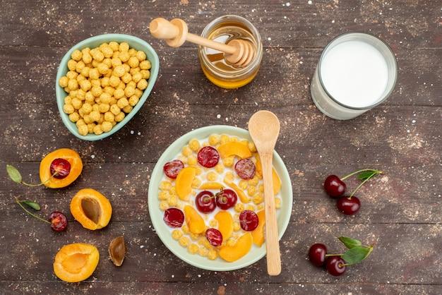 Вид сверху каши с молоком внутри тарелки со свежими фруктами и медом по дереву, хлопья из кукурузных хлопьев завтрак