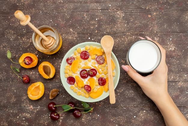 Вид сверху каши с молоком внутри тарелки со свежими фруктами медом и стаканом молока на дереве, хлопья из кукурузных хлопьев завтрак