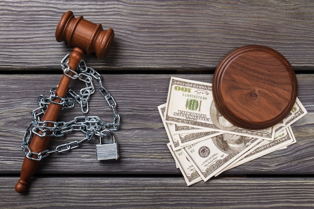 Top view chained gavel and dollars.