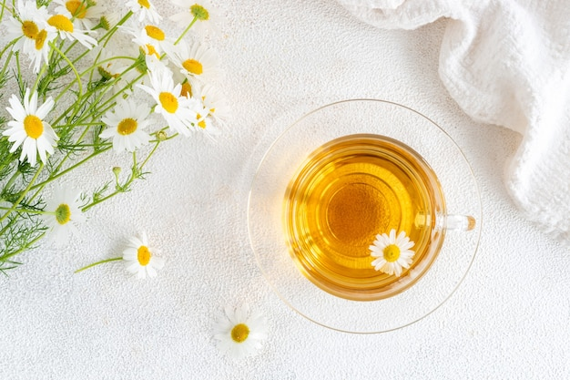 Top view of chamomile tea in a transparent mug with natural small chamomile flowers