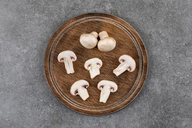 Vista dall'alto di funghi champignon. tritato o intero su tavola di legno