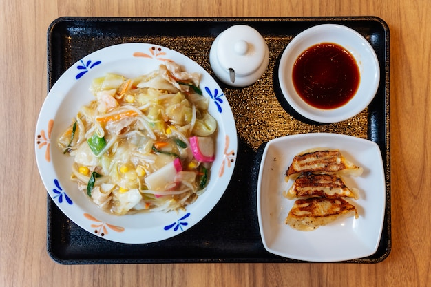 Top view of champon ramen (a noodle dish that is a regional cuisine of nagasaki, japan) served with yaki gyoza.