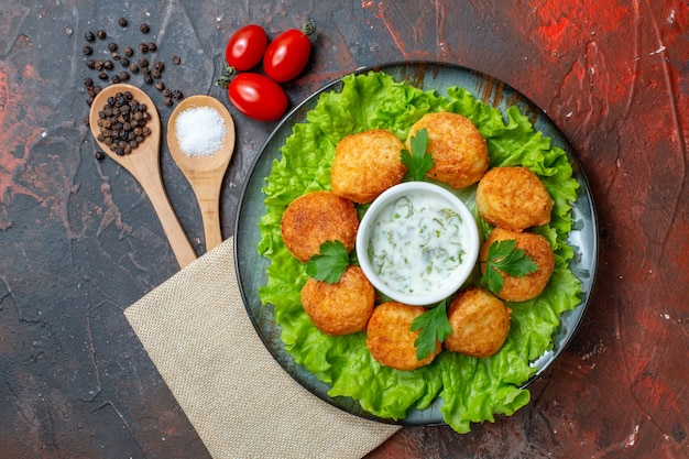 Top view cheese balls on plate with lettuce and sauce cherry tomatoes wooden spoons black peppers on dark surface