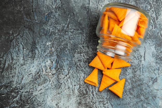Vista dall'alto di patatine al formaggio all'interno della latta di vetro su una superficie scura