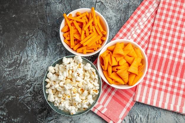 Vista dall'alto di patatine al formaggio con popcorn e fette biscottate sulla superficie chiara