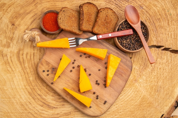 Top view cheese on fork slices of cheese on chopping board and slices of bread on wooden table