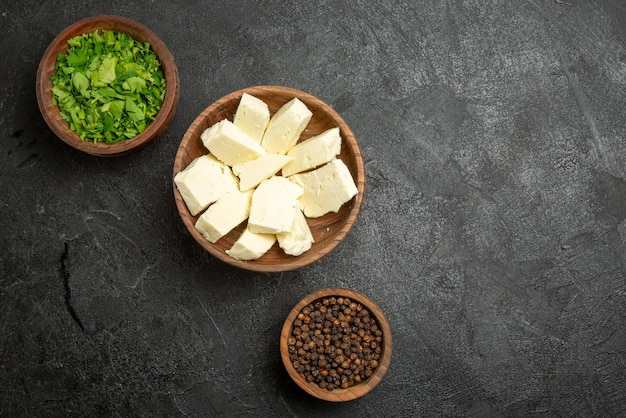 어두운 테이블에 검은 후추 허브와 치즈의 상위 뷰 치즈 허브 갈색 그릇