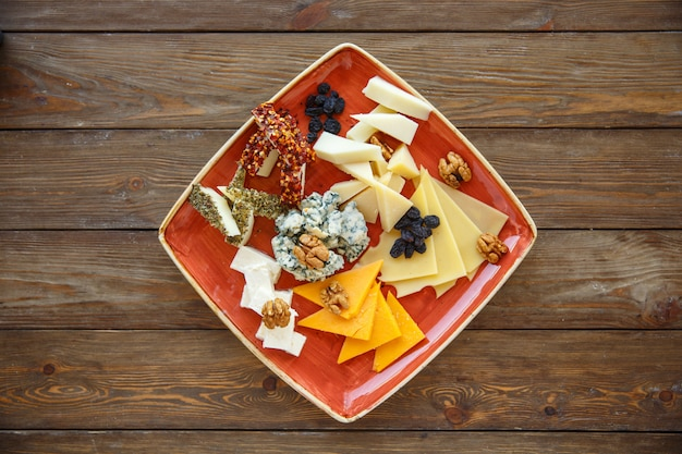 Top view of cheese plate with cheddar, gouda, white, and blue cheese