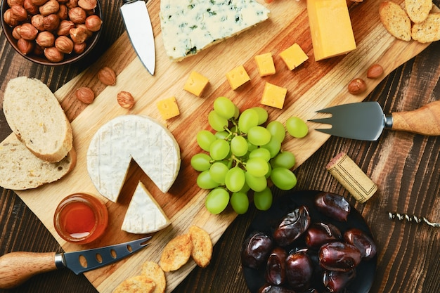 Top view of cheese plate with dorblu, brie, cheddar, grapes, honey, dates, crackers and nuts