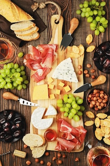Top view of cheese plate with dorblu, brie, cheddar, prosciutto, grapes, honey, dates, crackers, nuts and wine